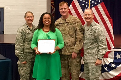 Woman holding document surrounded by service members