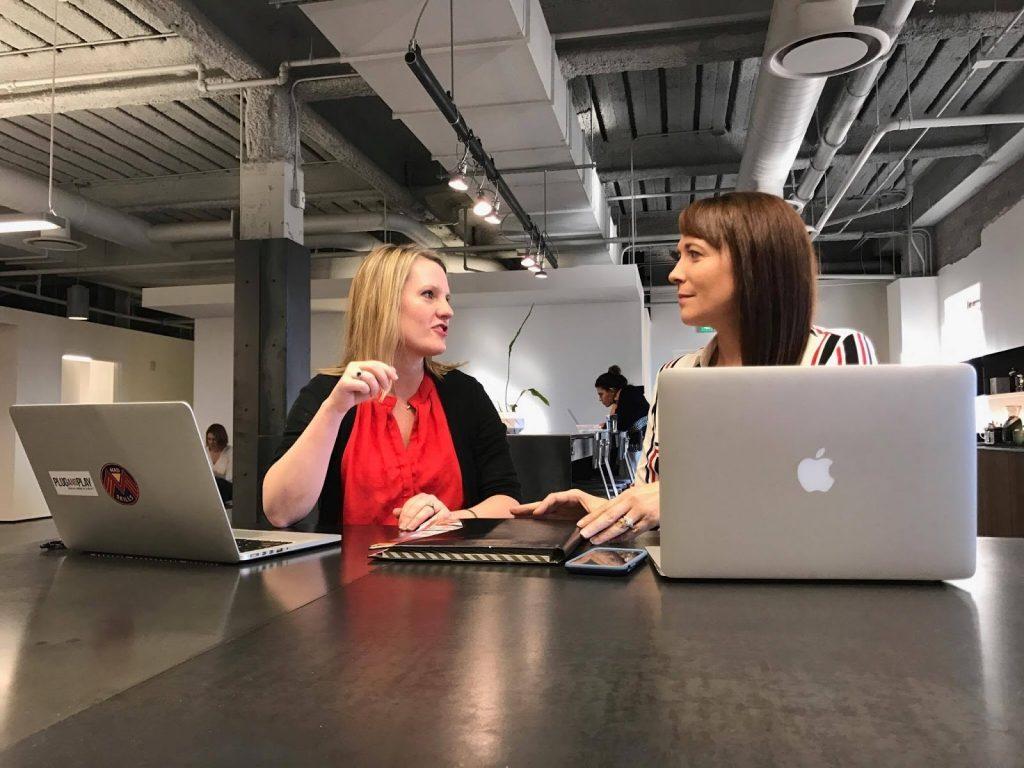 image of two women sitting at laptops talking