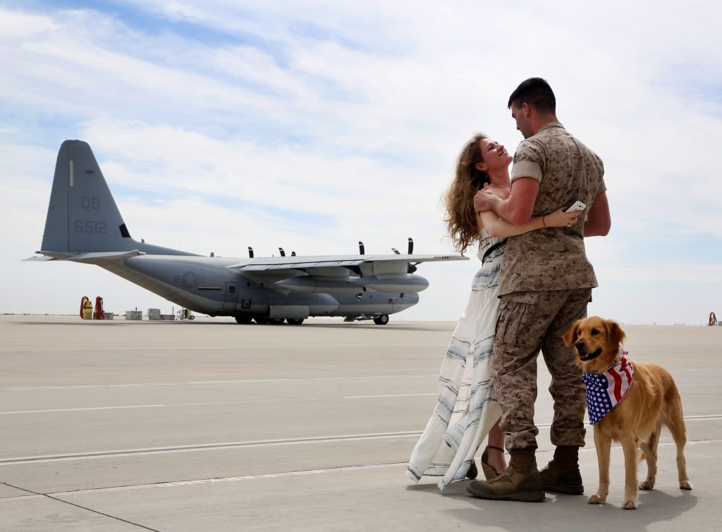 Marine hugging his wife with their dog on airfield
