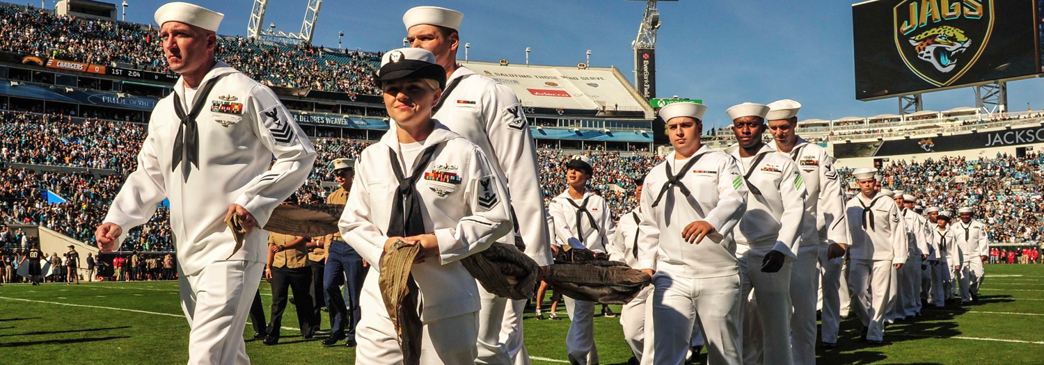 Sailors walking onto football field in Jacksonville