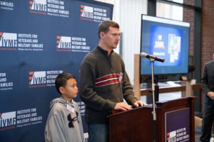 Nathan Smith speaking at podium with son by his side.