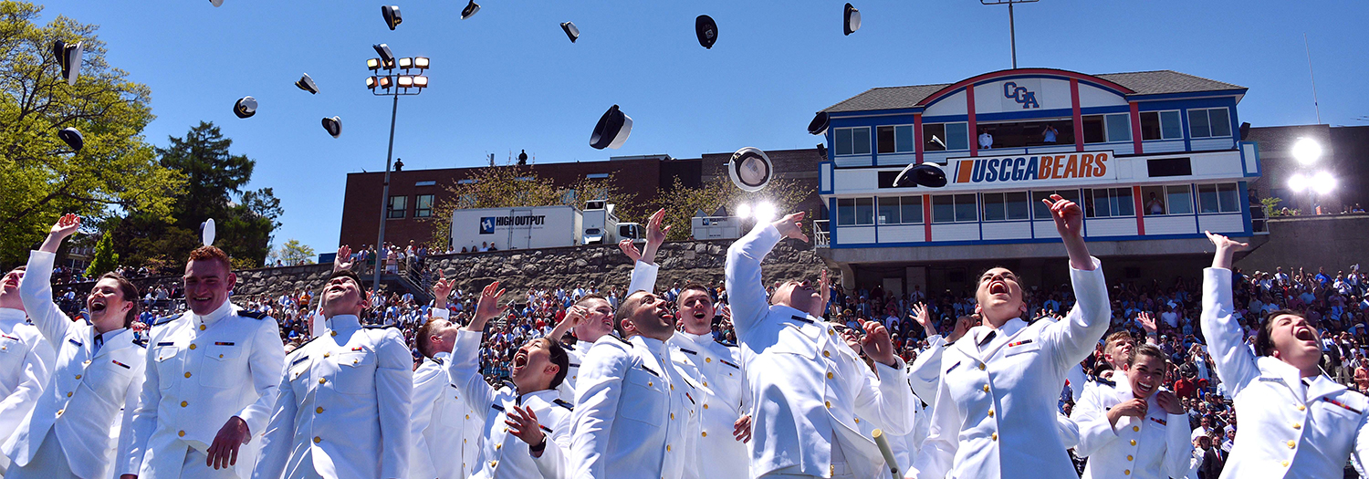 U.S. coast guard graduation with cadets throwing caps into the air.