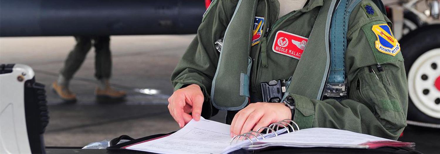 female pilot going over pre-flight notes.