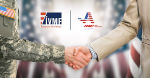 Soldier in uniform shaking the hand of a business man with IVMF and AARP logos present.