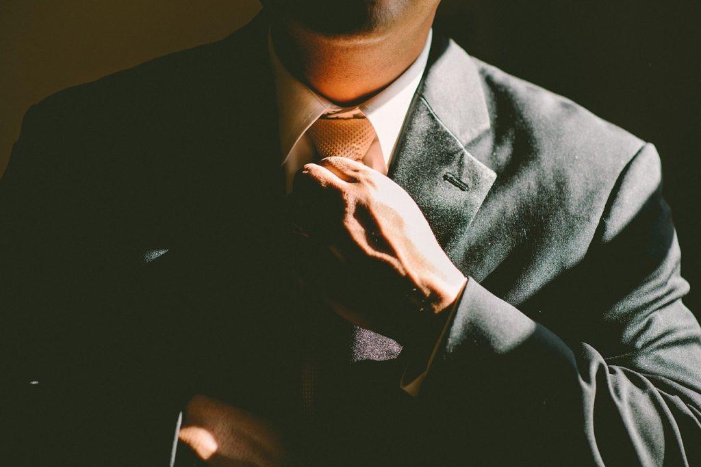a business man adjusting his tie.