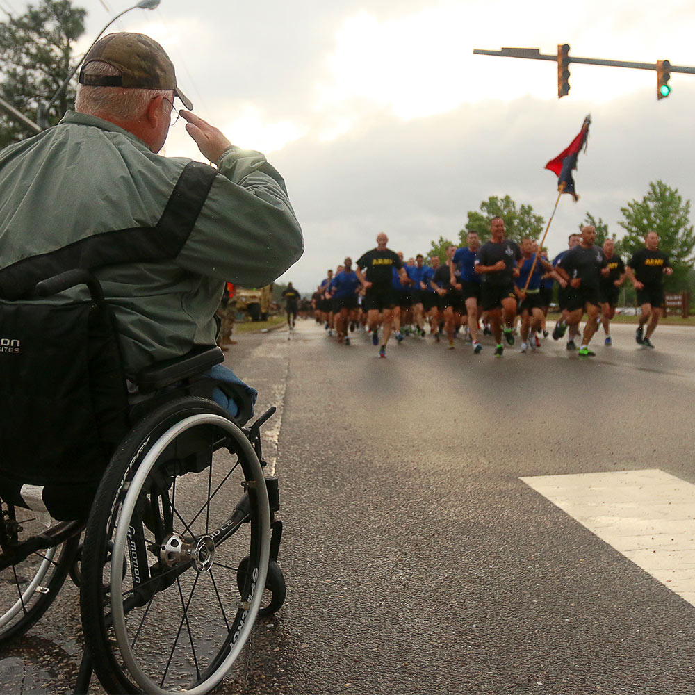 Veteran in wheelchair watching marathon runners.