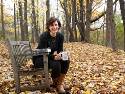 Jill Hinton sitting on bench in woods drinking coffee