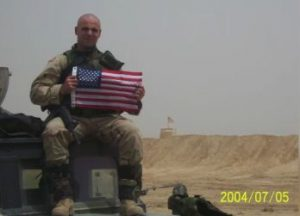 Brian Collins deployed holding american flag.